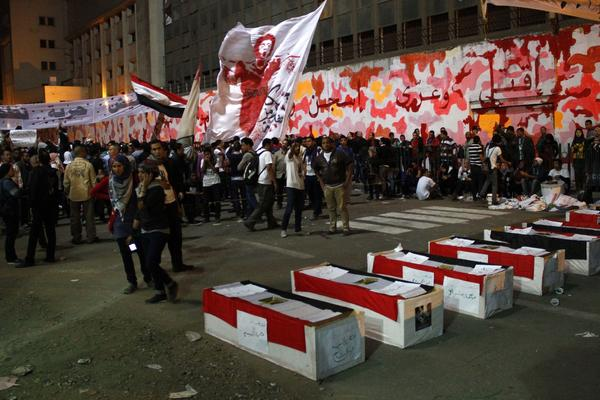 Egyptian protesters gather Tuesday in Mohammed Mahmoud Street just off Tahrir Square in Cairo alongside mock coffins representing the scores of people killed during clashes there in 2011 and 2012.