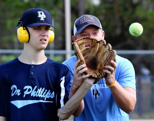 Dr. Phillips High School baseball player Nolan Lang (right) mentors Cameron Meena, who has autism, during a conditioning session at the school, Friday, Nov. 1, 2013.