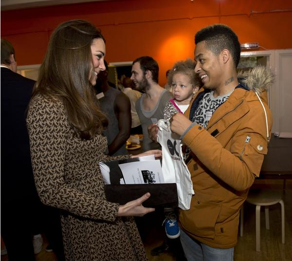 Catherine, Duchess of Cambridge, is presented with a onesie for her son Prince George of Cambridge from Aaron Russell-Andrews and his daughter Teegan at the Only Connect charity.
