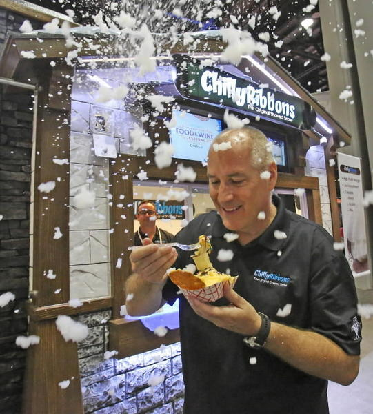 Scott Colwell, CEO of Orlando-based Chilly Ribbons, tastes a mango shaved ice treat as a machine near the roof of the small kiosk modeled after a ski chalet spews fake snow. Colwell's company is attending IAAPA at Orange County Convention Center.