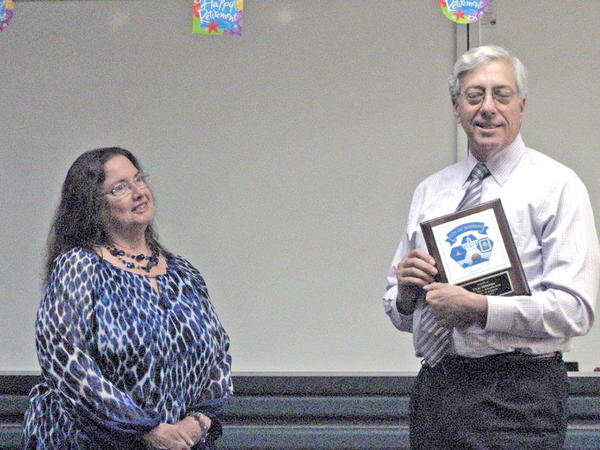 City Manager Mark Scott presents a plaque to Vicki Miskimin, who has retired from the Burbank Police Department.