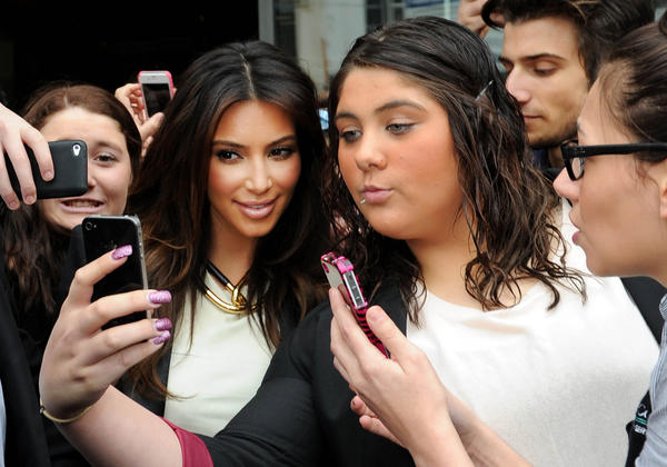 "In this photo from Sept. 21, 2012, Kim Kardashian is surrounded by fans attempting to take photos of themselves with her as she leaves a radio station in Melbourne, Australia. England's Oxford University press declared ""selfie"" the word of the year for 2013 on Tuesday."