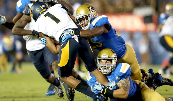 UCLA's Ryan Hofmeister, bottom, grabs at California's Bryce Treggs' feet to pull down the wide receiver during the Bruins' 37-10 win on Oct. 12.