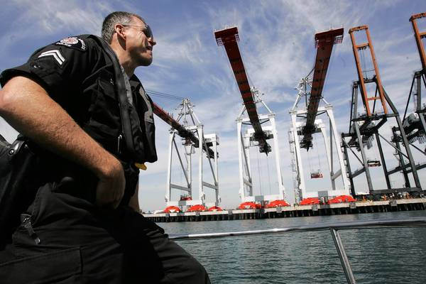 A port police officer patrols near the TraPac terminal in Wilmington; the price tag for an upgrade at the terminal has ballooned.