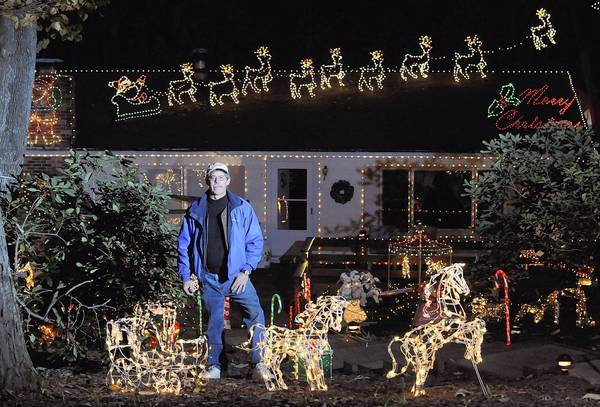 Chuck Greason stands outside his Parkton home that has become a showcase for his Christmas display of lights and trains. Greason asks visitors to donate canned goods and non-perishables to the North Cluster Food Bank.
