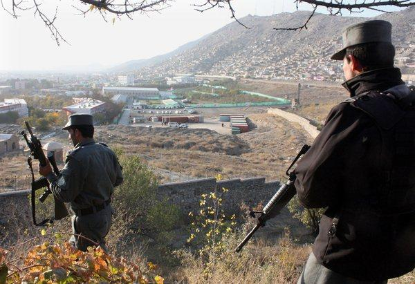 Afghan policemen patrol a hillside overlooking the venue where a loya jirga will be held Thursday in Kabul, Afghanistan.