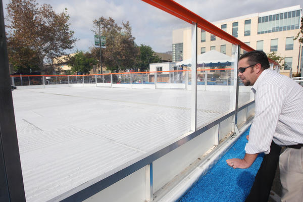 Burbank Water & Power employee Chris Allen takes a look at the ice forming on a temporary skating rink that was installed behind City Hall, photographed on Tuesday, Nov. 19, 2013.