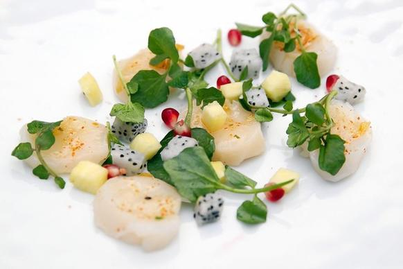 The wild Maine day boat scallop sashimi dish at Oceanique in Evanston. The dish is served with arugula, dragon fruit, yuzu, and pomegranate.