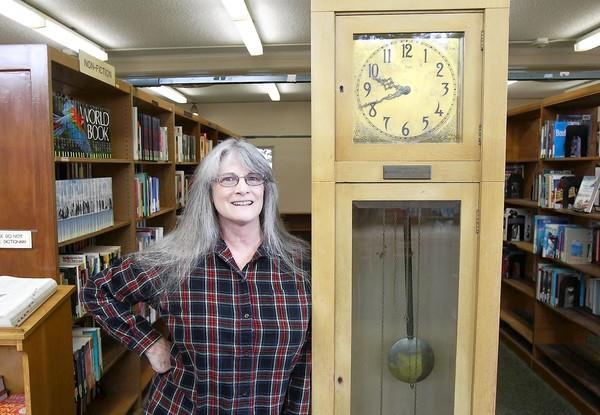 Branch manager Robin Ott stands next to one of the Main Street Library's most popular items, a 1915 grandfather clock built by students from Huntington Beach High School in 1915.