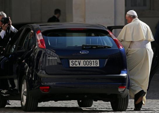 Pope Francis climbs into the back seat of a Ford Focus following his ...