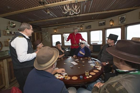 Living history characters and passengers play cards in the SS Legacy's Pesky Barnacle Saloon.