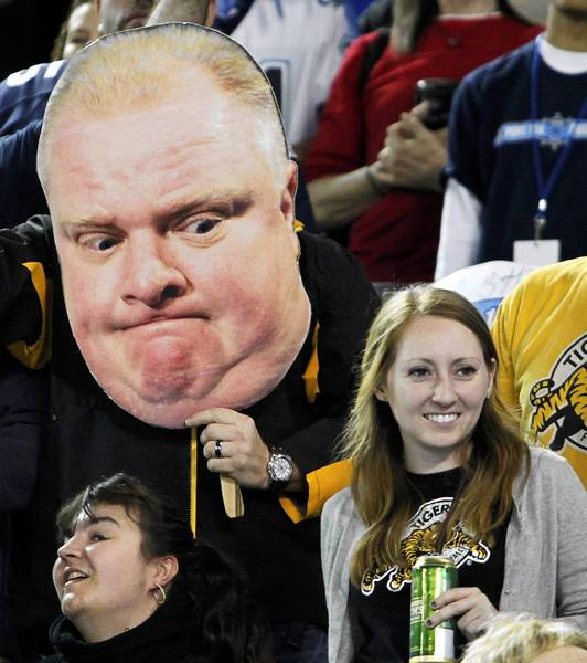 A football fan holds a cutout poster of Toronto Mayor Rob Ford during a Canadian Football League game in Toronto last month.