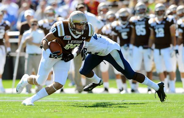 lehigh's Lee Kurfis (front) slips out of a tackle from New Hampshire's Akil Anderson (back) during their college football game Saturday, September 28, 2013.