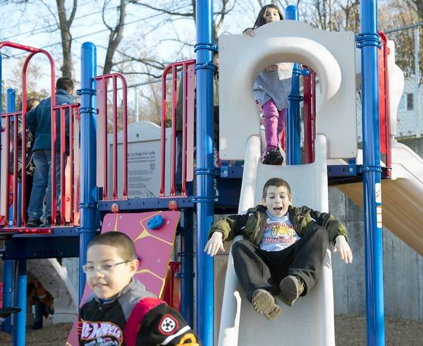 5th grader Edgar Akhmeov goes down a slide as Fountain Hill Elementary School holds a playground dedication ceremony at the school on Wednesday.