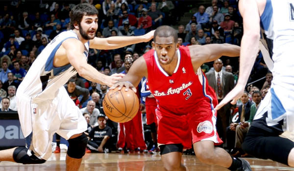 Chris Paul drives toward the hoop in front of Minnesota's Ricky Rubio en route to his 12th consecutive double-double in a win over the Timberwolves, 102-98.