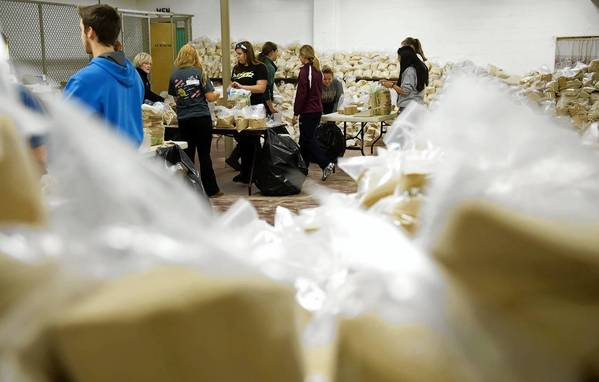 Students from Freedom and Liberty high schools meet at the Bethlehem Memorial Pool Building Monday night, packaging sand, candles and bags for Luminaria Night.