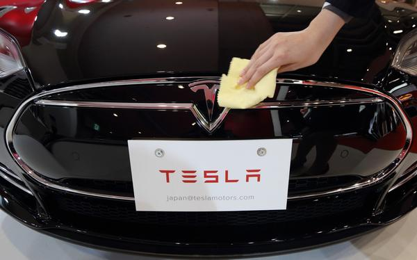 A staff member makes sure the Tesla Model S electric vehicle is ready for the 43rd Tokyo Motor Show.