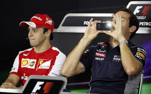 Red Bull Formula One driver Mark Webber (R) of Australia takes a photograph next to Ferrari Formula One driver Felipe Massa of Brazil before a news conference ahead of the Brazilian Grand Prix.