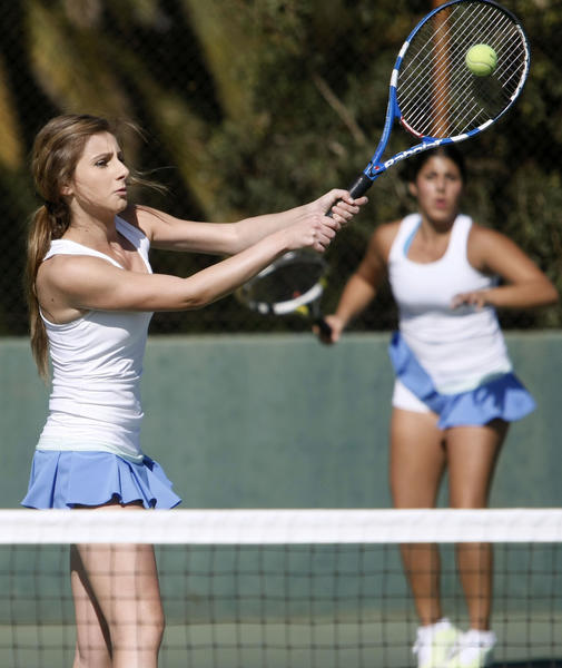 Crescenta Valley High School doubles player Jackie Dilanchyan returns one as teammate Alexa Gregorian looks on in the background during Pacific League tennis playoff game at Pasadena High School in Pasadena on Wednesday, Oct. 30, 2013.