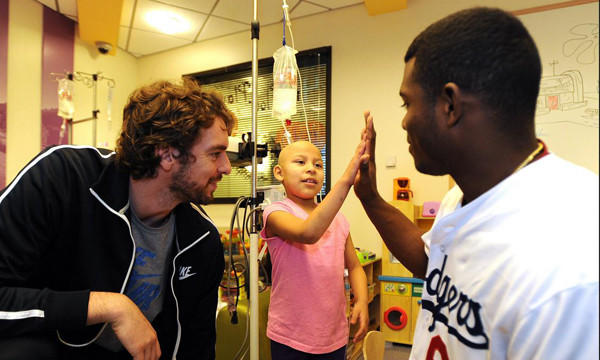 The Lakers' Pau Gasol, left, and the Dodgers' Yasiel Puig visit a patient while at Children's Hospital Los Angeles on Tuesday.