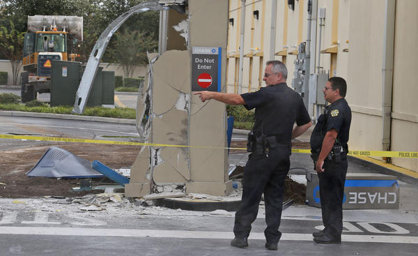 Orlando Police officers secure a crime scene Thursday, November 21, 2013 at a Chase Bank ATM drive-thru in east Orange County. Someone used a construction front end loader, background, left, to remove the Chase ATM machine.