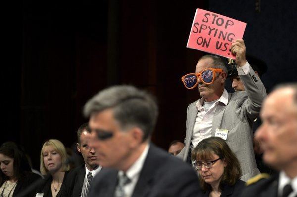 A protester stands at a House Select Intelligence Committee hearing on potential changes to the Foreign Intelligence Surveillance Act on Capitol Hill.