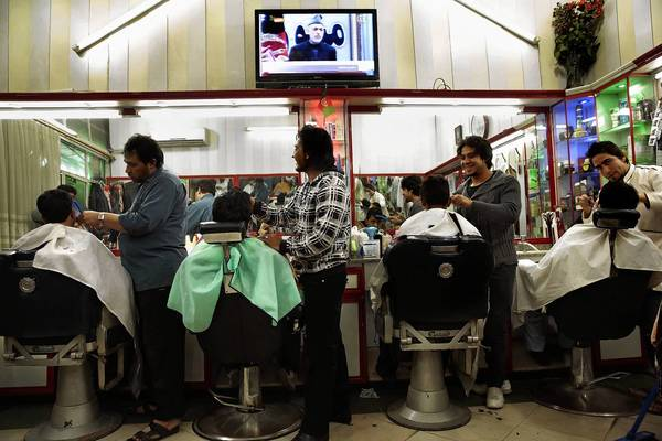 A barbershop in Kabul carries the speech by Afghan President Hamid Karzai. His comments left the U.S. wondering whether he was grandstanding or angling for more concessions in the nations' security agreement.