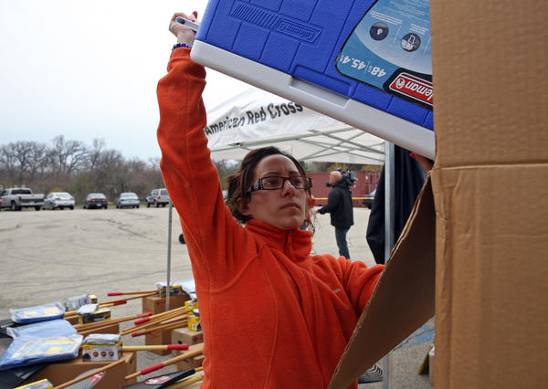 An American Red Cross volunteer unloads coolers during a clean-up kit distribution to North Side residents at Gompers Park in April 2013.
