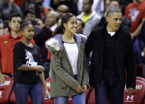 President Obama walks to his seat with daughters Sasha, left, who is clad in the much-coveted Asos sweater, and Malia before a basketball game between Maryland and Oregon State in College Park, Md.