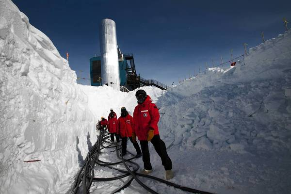Members of the IceCube scientific team pull cables during the construction of the neutrino-detecting telescope beneath the South Pole in December 2010.