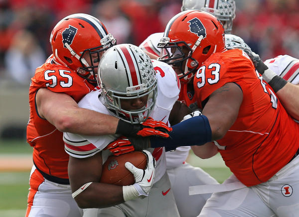 Ohio State's Carlos Hyde drags tacklers Houston Bates and Teko Powell.