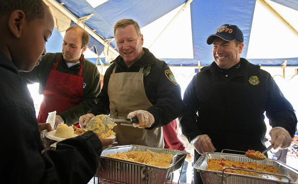 Jacorae Whiting, left, is served by volunteers from the Newport News Police Department at the 2012 Feeding 5000 Thanksgiving Harvest and Community Celebration event in Newport News