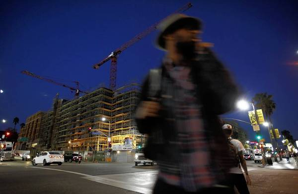 Pedestrians walk by the construction site of the Blvd6200 development at Hollywood Boulevard and Argyle Avenue. Los Angeles officials did not require a seismic study for the site. Several geologists said uneven water levels beneath the site should have prompted further investigation.