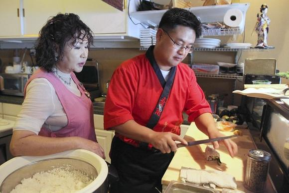 Owner Gina Pak (left) watches chef Sung Kook Cha make sushi at Sushi Lola's.
