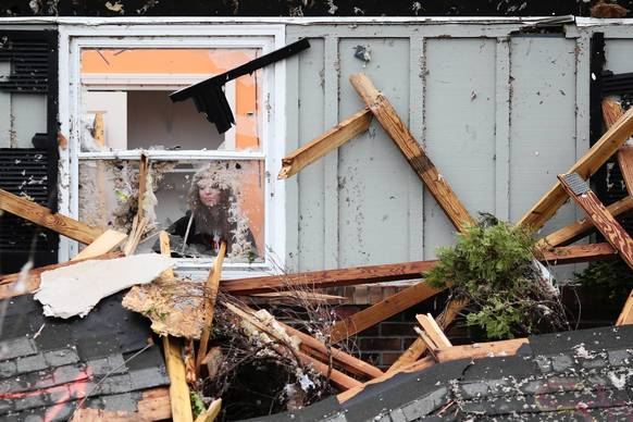 Zoe Volk, 19, looks out a window at the family home of her friend Maura O'Brien whose home was destroyed by the Nov. 17 tornado that tore through Washington, Illinois.