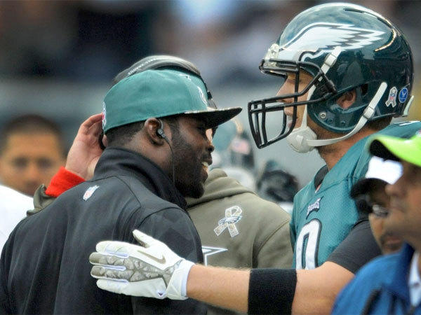 Philadelphia quarterback Nick Foles, right, is congratulated by injured starter Michael Vick after scoring a rushing touchdown against the Washington Redskins