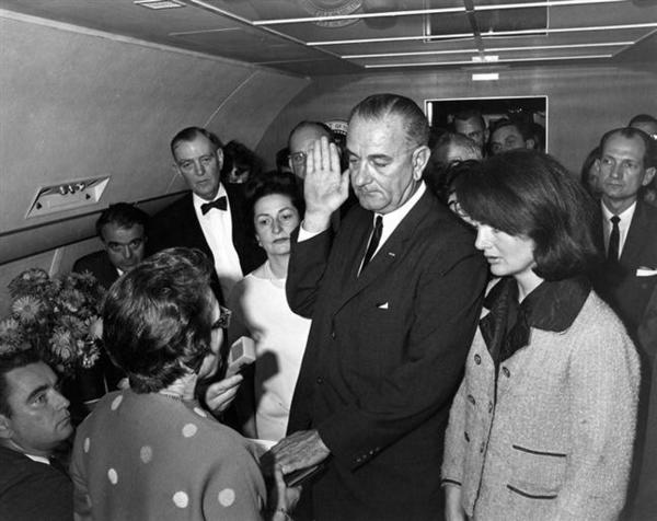 This file photo dated November 22, 1963 courtesy the John F. Kennedy Presidential Library and Museum, Boston, shows Judge Sarah T. Hughes administering the Presidential Oath of Office to Lyndon Baines Johnson aboard Air Force One, at Love Field, Dallas Texas as Lady Bird Johnson (C-L), Jacqueline Kennedy (R), Jack Valenti, Cong. Albert Thomas, Cong. Jack Brooks, and Associate Press Secretary Malcolm Kilduff (holding microphone) witness the event. (Cecil Stoughton/White House)