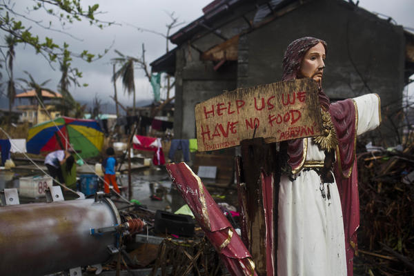 A plea for help painted on a sign hangs from a damaged statue of Jesus in Tacloban, Philippines. Officials disclosed Friday that the death toll has climbed to 5,209 and ordered a speed-up of rebuilding to house the 4 million left homeless by the Nov. 8 storm.