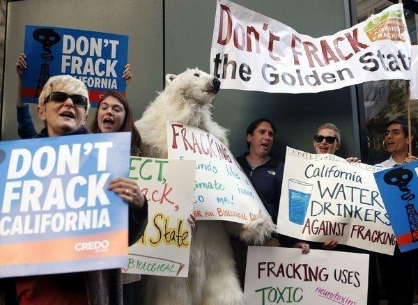 Environmental demonstrators in September protest Gov. Jerry Brown's position on natural gas fracking before Brown arrived for a news conference in San Francisco. The governor has released draft regulations on fracking that are based on a bill passed earlier this year by the state Legislature.