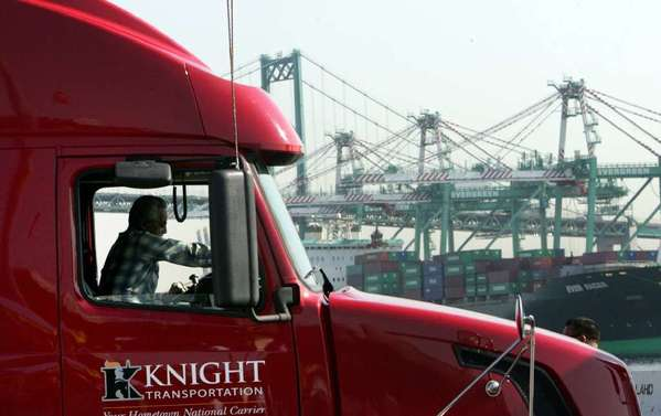 A truck driver is seen in San Pedro with the Port of Los Angeles in the background. Some port truckers recently called a one-day strike to protest their working conditions.