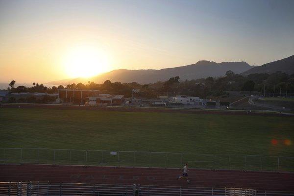 At sunset, a runner makes his way around the Malibu High School track in July. Preliminary testing at the school has uncovered elevated levels of toxins, district officials said.
