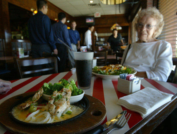 Shirley Booker sits at a table at TGI Fridays in Los Angeles. The chain might be sold, its parent company Carlson said.