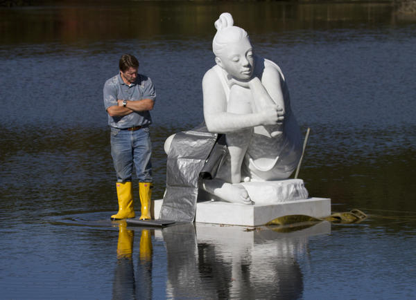 "Steven Jenson ponders his next move during the installation of the sculpture Selene at the Kettle pond in Newport News. ""Selene,"" a 7-foot, 8,455-pound figure sculpted by Italian artist Maria Gamundi, is the Newport News Public Art Foundation's latest project."