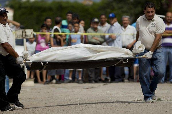 Forensic investigators in Honduras carry the body of a man who was killed in a shootout with police on a residential street in Tegucigalpa this month. Candidates running for president in an election Sunday have been promising to control violence.
