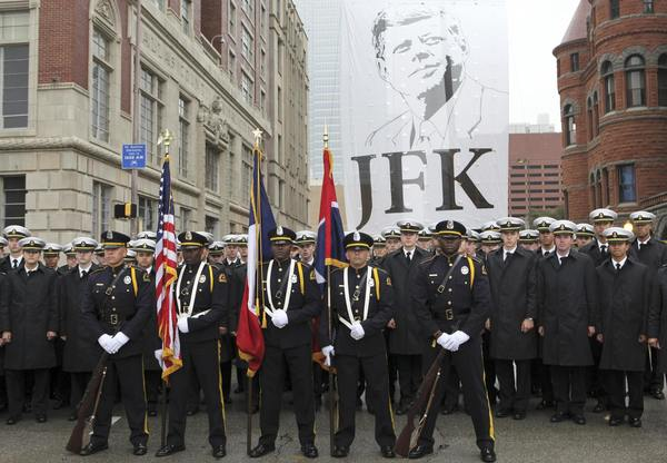 The Dallas Police Department Honorary Color Guard and the U.S. Naval Academy Men's Glee Club pose in front of a giant JFK banner at the conclusion of ceremonies commemorating the 50th anniversary of the death of President John F. Kennedy in Dealey Plaza in Dallas, November 22, 2013.