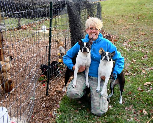 Salon owner Kellie Johnson holds her Boston terriers Skippy and Marley.