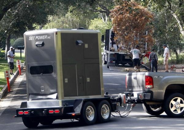 Film production crews unload trees as other crews arrive with portable power at 4159 Commonwealth Ave., in La Canada Flintridge. Some neighbors do not like the frequency of filming at this home.