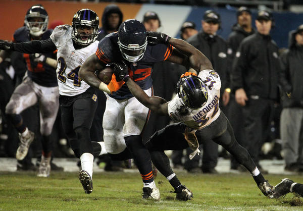 The Ravens' James Ihedigbo attempts to take down Martellus Bennett during the fourth quarter.