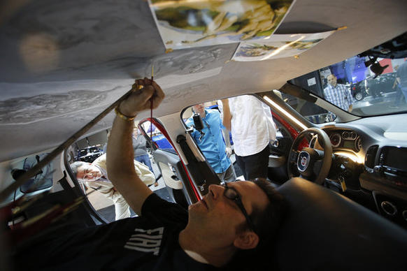 Italian-born artist Nicola Verlato paints a scene from Michaelangelo's Sistine Chapel fresco on the ceiling of a new Fiat 500L on the opening day of the Los Angeles Auto Show.
