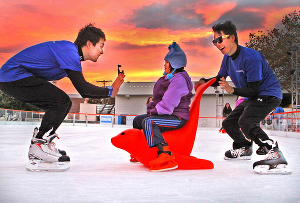 Jeremy Steele and Jourdan Steele, twins, who are skate guards at Ice America, pull Lisa Truong, 7, of North Hills on a red seal on an ice rink behind Burbank City Hall on Friday, Nov. 22, 2013. The rink, which had a grand opening this week, has had about 100 skaters so far, and will remain open through January 5.